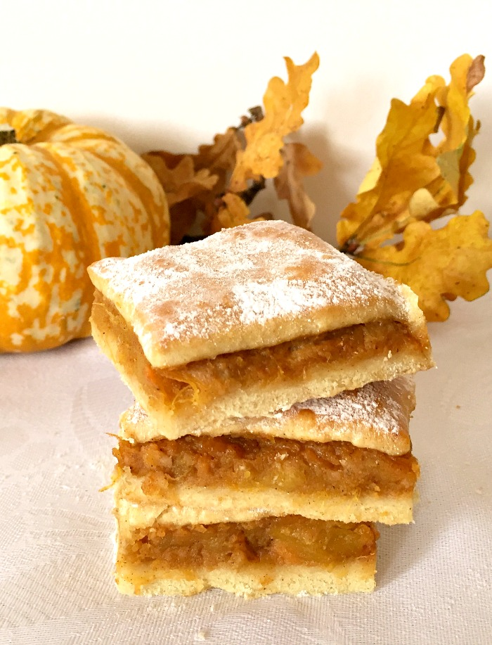 A stack of 4 pumpkin squares on a white table cloth, with a pumpkin and dry leaves in the background