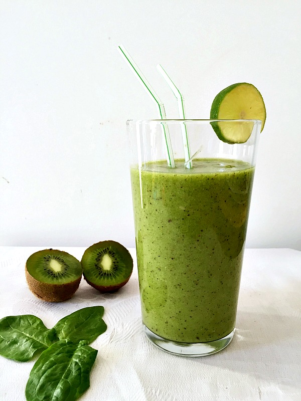A glass of kiwi spinach smoothie with 2 halves of kiwi and 3 spinach leaves next to it