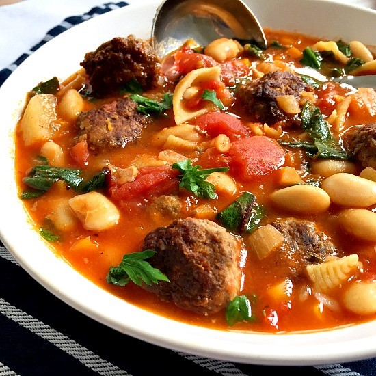 A white plate with minestrone and meatball soup