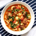 Overhead shoot of a white bowl with meatball minstrone soup