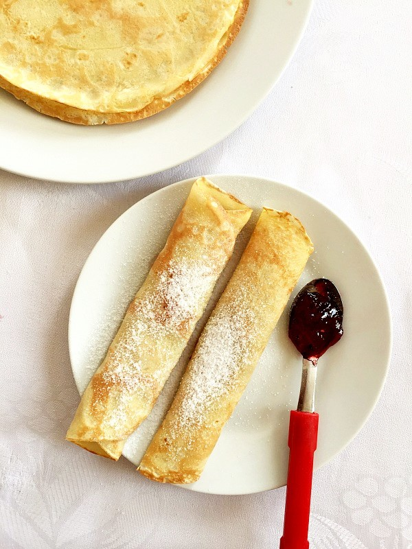 Overhead shot of 2 rolled French crepes on a white plate with a teaspoon of strawberry jam next to it