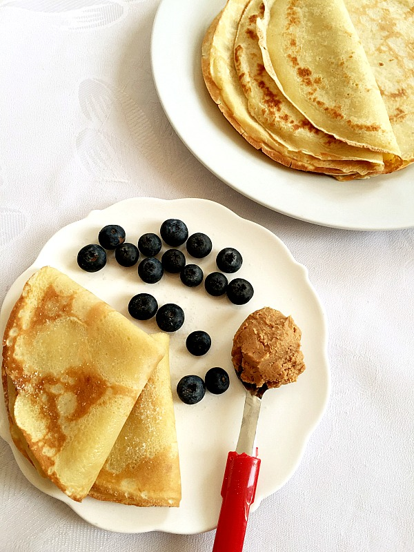 A white plate of 2 folded french crepes with blueberries and a spoonful of peanut butter