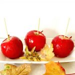 Red Candy Apples, a favourite Fall treat that is perfect for a Halloween trick-or-treat bag. They might not be too spooky, although the bright red looks pretty bloody. Kids will love them, they look fun and making them at home from scratch is super easy. A childhood treat that brings back sweet memories every single time. Learn how to make these easy candy apples in any colour you like. #redcandyapples, #candyapples, #halloweenfood, #fallrecipes, #thanksgiving, #kidstreats