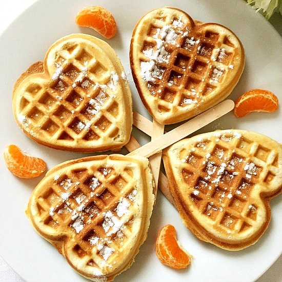 4 heart-shaped cinnamon waffles on a white plate with 4 clementine slices in bewtween each waffle