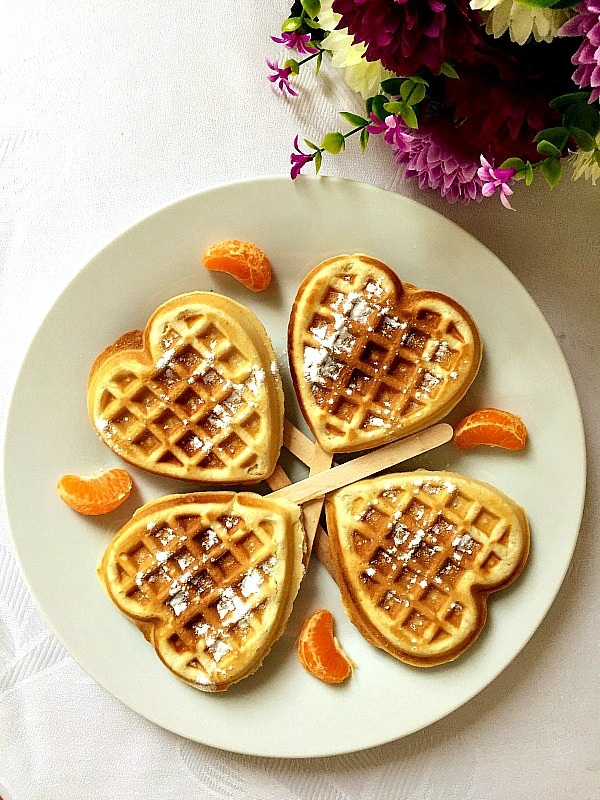 4 heart-shaped waffles on a white plate with 4 slices of clementines in between them