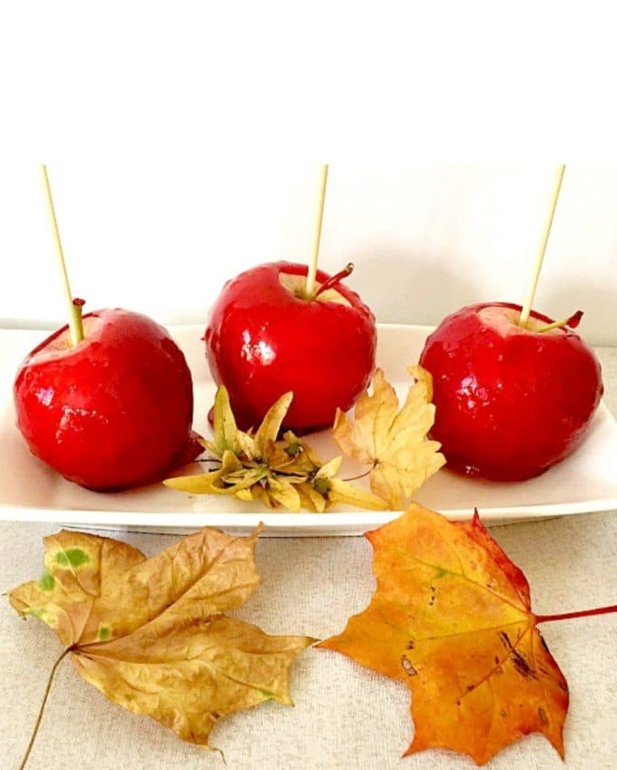 3 red candy apples on a white plate with yellow leaves around