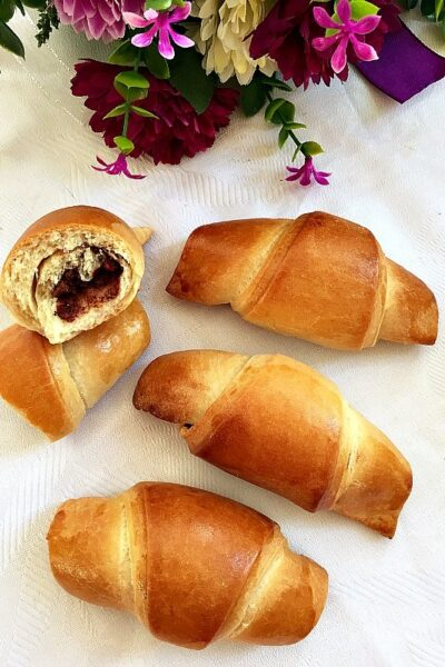 3 full croissants and two halves of a chocolate croissant on a tablecloth
