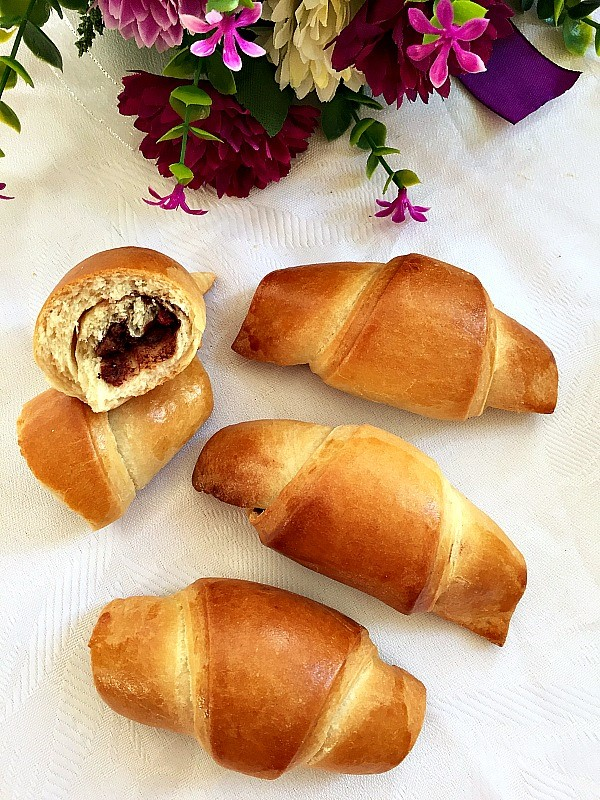 Overhead photo of 3 croissants and 2 halves of a croissant on a white table cloth with some flowers next to them