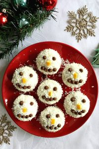 Coconut Snowman Cupcakes, the best Christmas cupcakes for kids and grown-ups alike. Moist and fluffy coconut cupcakes made from scratch, topped with a delicious coconut cream cheese icing, and decorated with chocolate chips and orange peel for a festive touch. Super easy to make, ready in no time, and gone from the plate in seconds. #christmasdesserts, #coconutcupcakes, #snowmancupcakes, #coconuticing, #festivetreats