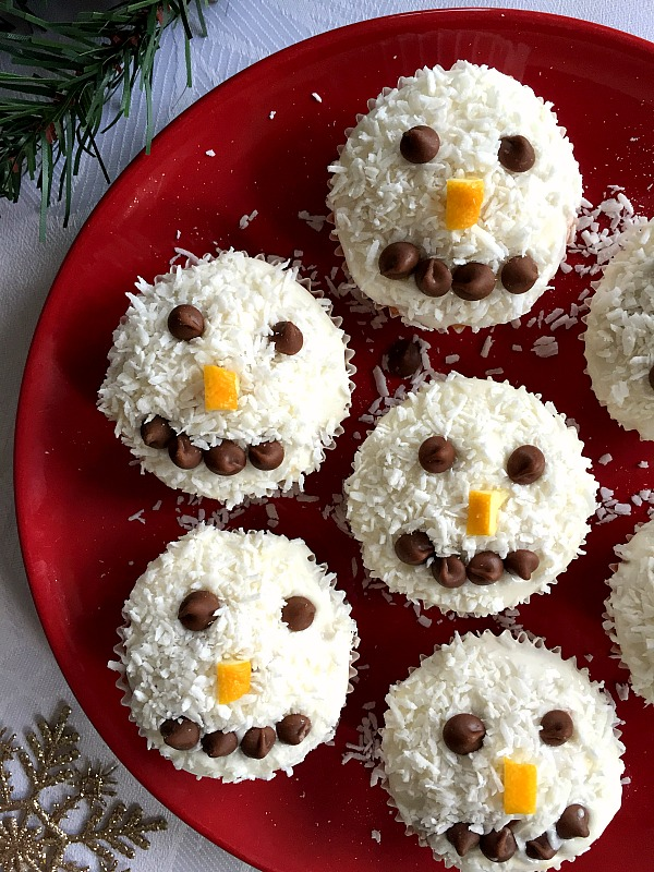 A red plate with 5 coconut snowman cupcakes