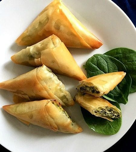 4 Spanakopita triangles and 2 halves of a triangle on a white plate