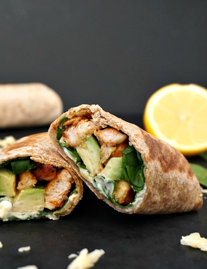 2 grilled chicken avocado wraps with a half a lemon in the background and a full wrap