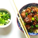 Overhead shot of a blue bowl of grilled teriyaki chicken with wooden chopsticks on the side and a small white bowl of chopped spring onions
