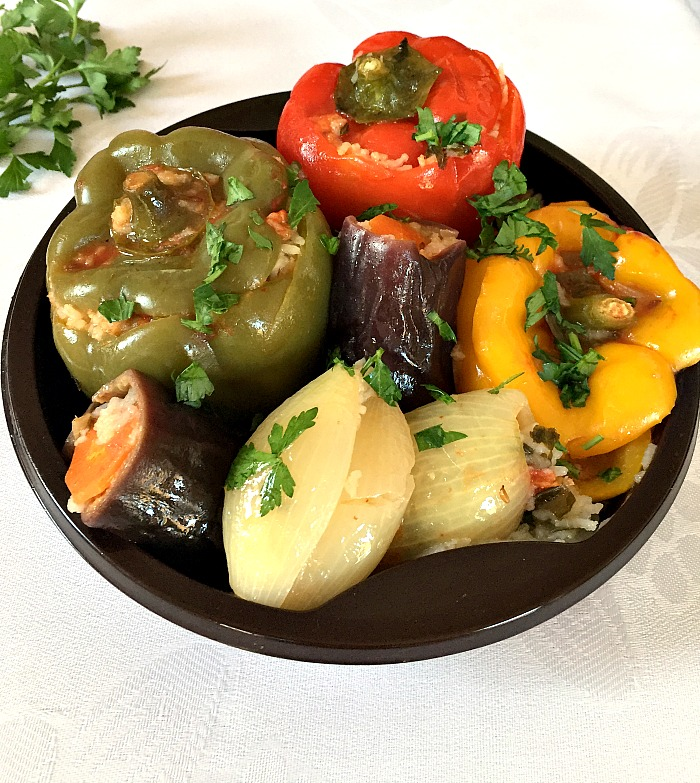 A black plate with middle eastern vegetarian dolma