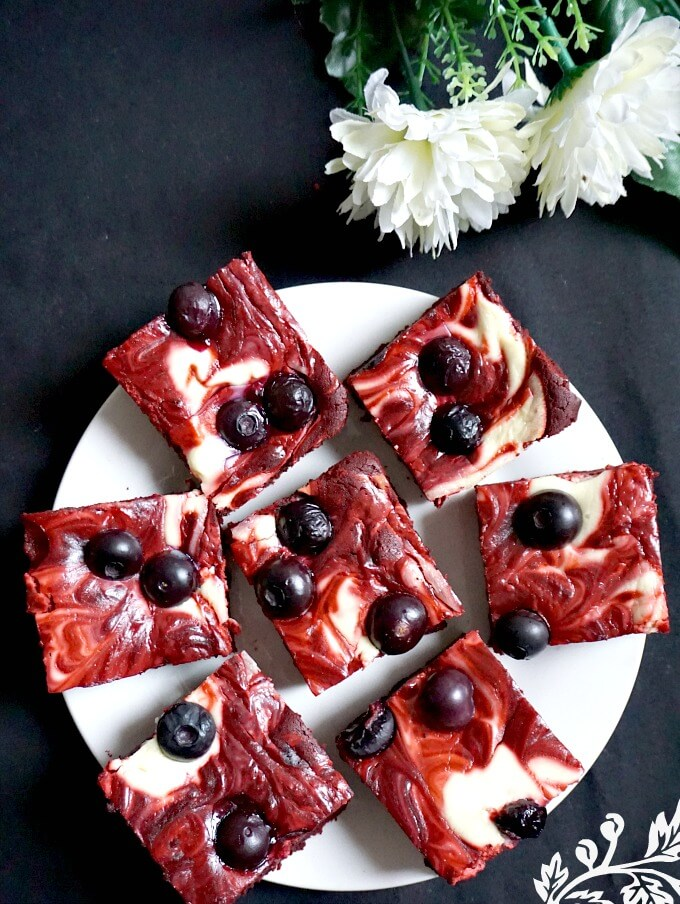 Overhead shot of a white plate with 7 red velvet cheesecake swirl brownies