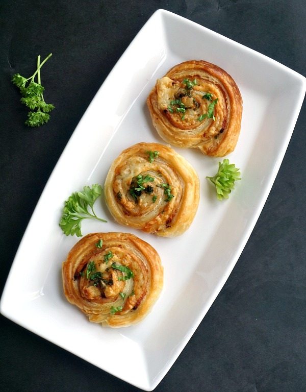 3 Puff Pastry Pinwheels with Ham and Cheese on a white serving plate with parsley leaves around