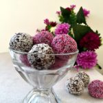 A glass bowl with brigadeiros and flowers in the background