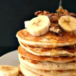 A stack of american pancakes topped with banana slices and walnuts, and drizzled with honey