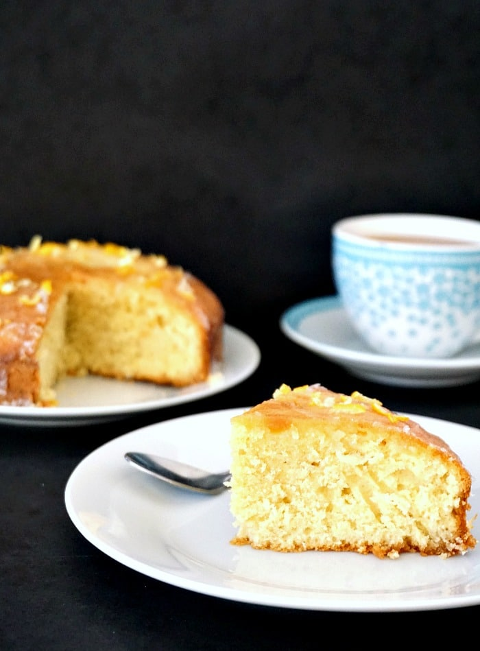A slice of Lemon Drizzle Cake on a white plate, with a cup of tea in the background and a large plate with the rest of the cake.