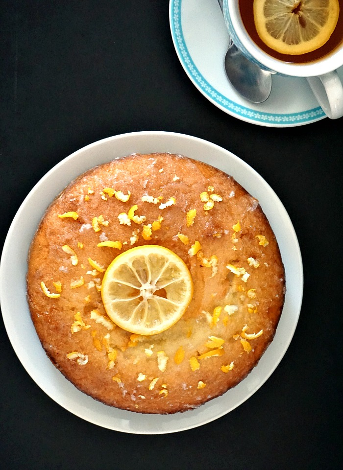 Overhead view of a white plate with a lemon drizzle cake topped with a slice of lemon
