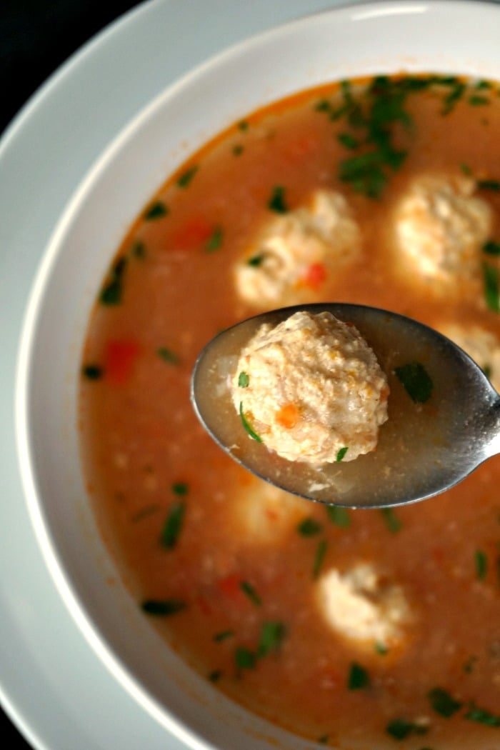 A close shot of a meatball in a spoon over a white bowl of Romanian Meatball Soup