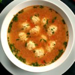 Overhead shot of a while bowl of Romanian Meatball soup arranged on a while plate
