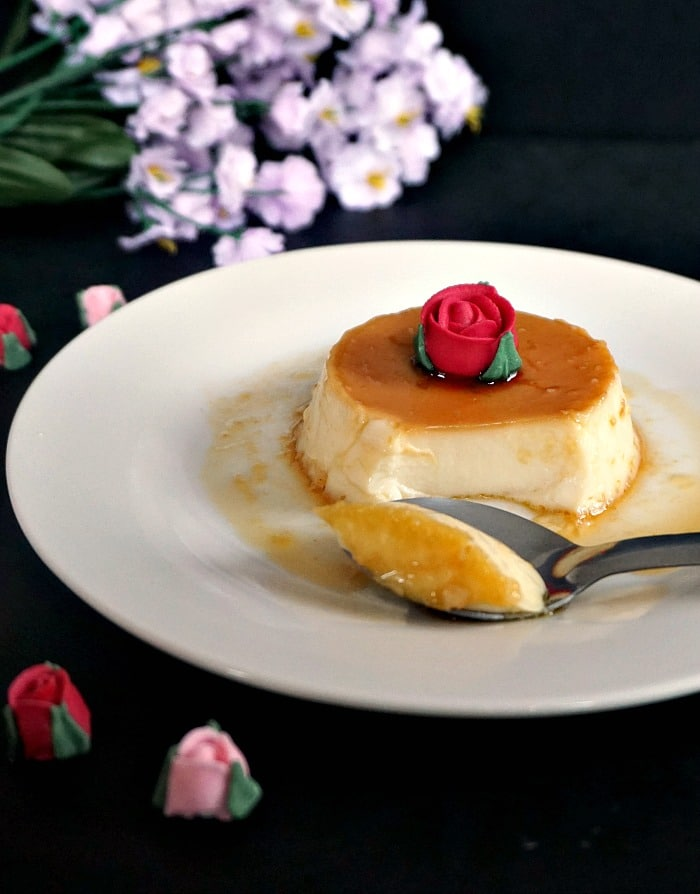 A white plate of creme caramel or flan with a teaspoon next to it