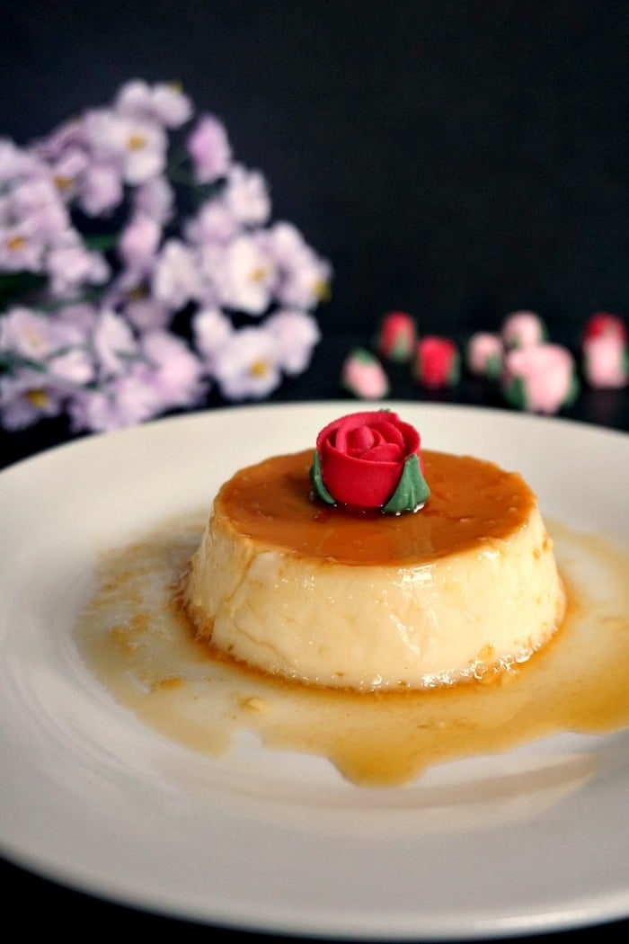 A white plate of a flan dessert topped with an edible red rose