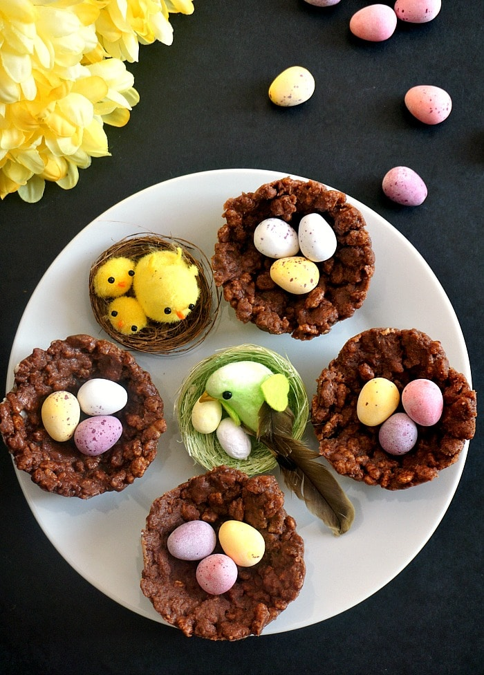 Overhead shot of a white plate with 4 rice krispies nests and 2 bird nests, mini Cadbury eggs and flowers around the plate