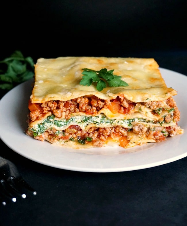 A large slice of turkey lasagna on a white plate