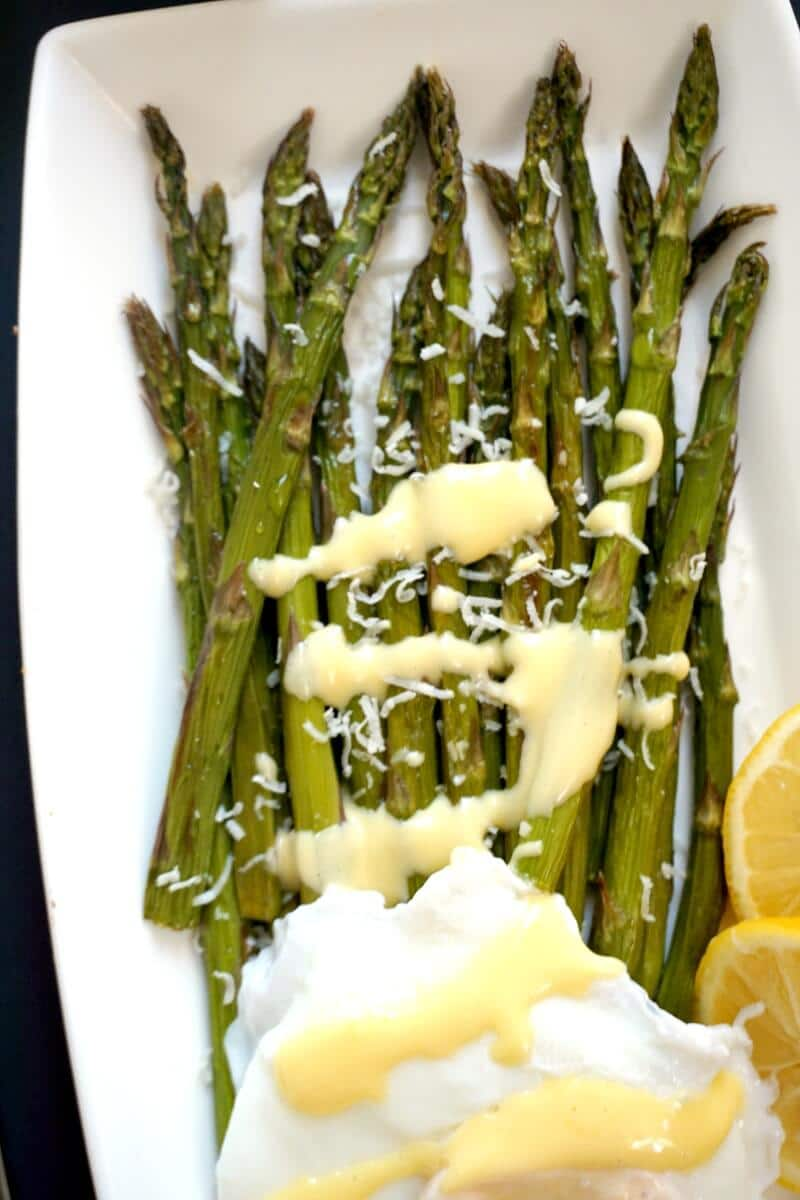 Overhead shoot of a rectangle white plate with roasted asparagus, hollandaise sauce and poached egg