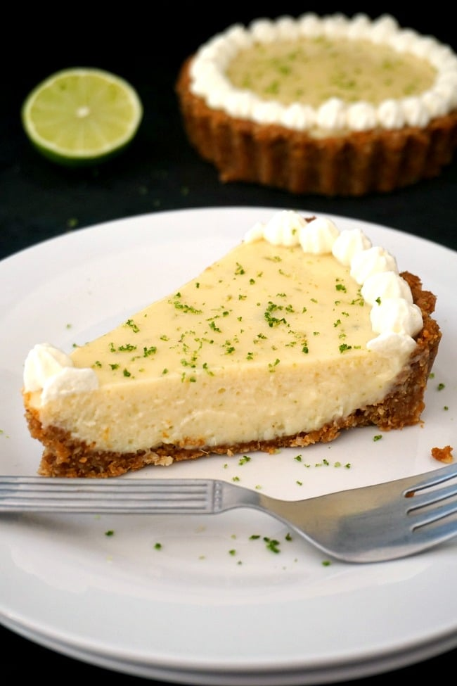 A slice of key lime pie with condensed milk on white plates with a fork next to it, a key lime pie and a slice of lime in the background