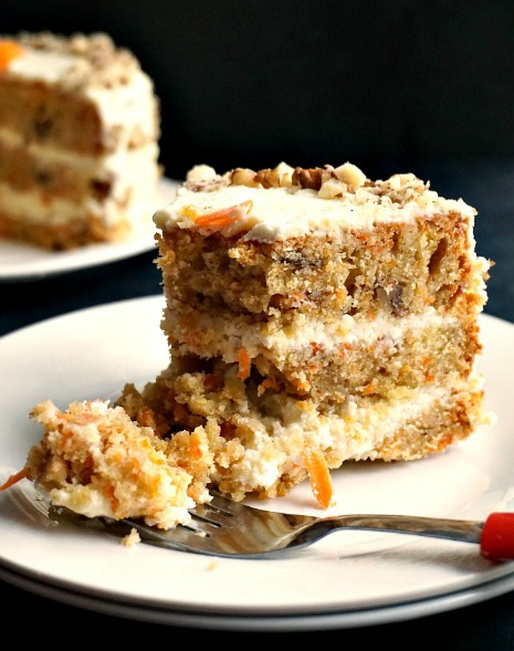 A slice of super moist carrot cake on two white plate with a fork next to it