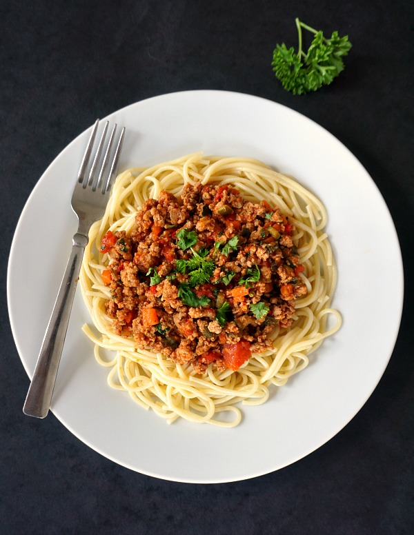 Overhead shot of a white plate of spaghetti bolognese with a fork on the side