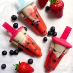 Overhead shoot of 3 red white and blue popsicles with blueberries and strawberries scattered around them