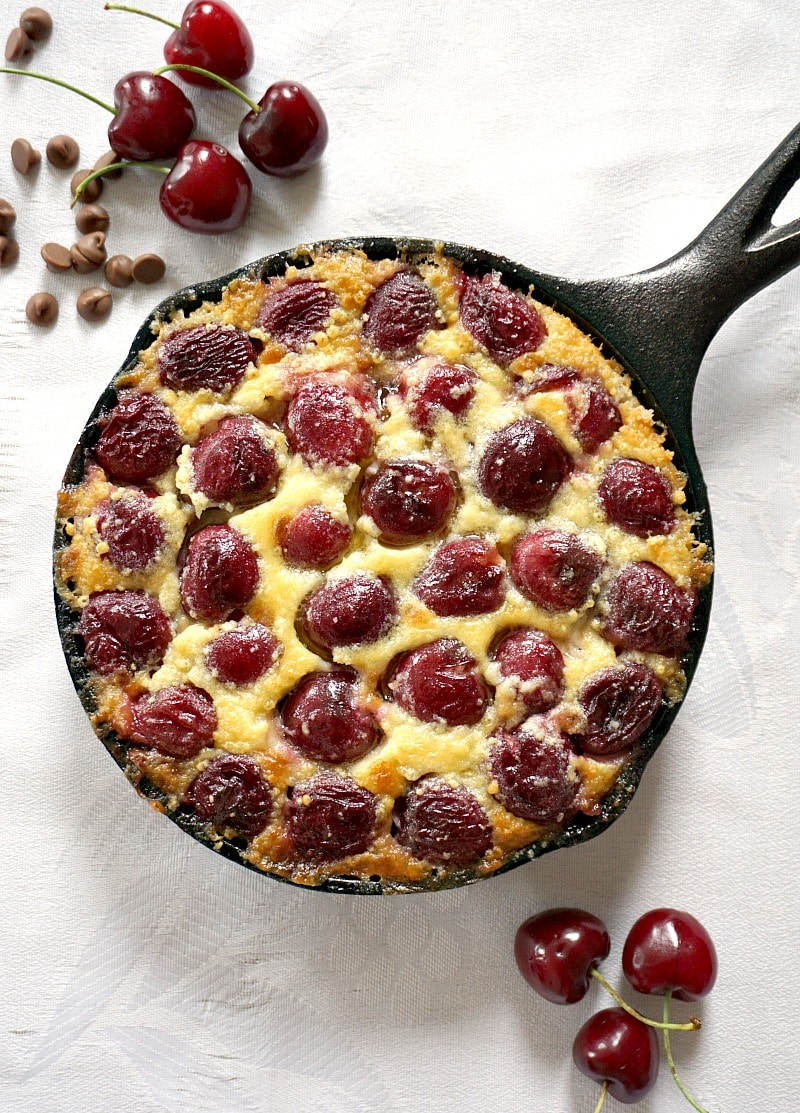 Overhead shot of a skillet of chery clafoutis with cherries and chocolate chips around