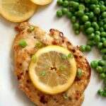 A chicken breast topped with a lemon slice, 2 slices of lemon on the side and peas
