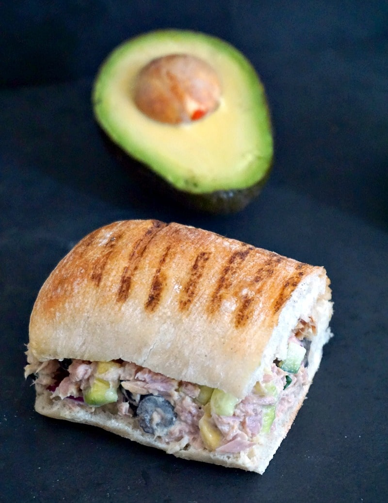 A tuna salad sandwich and half an avocado