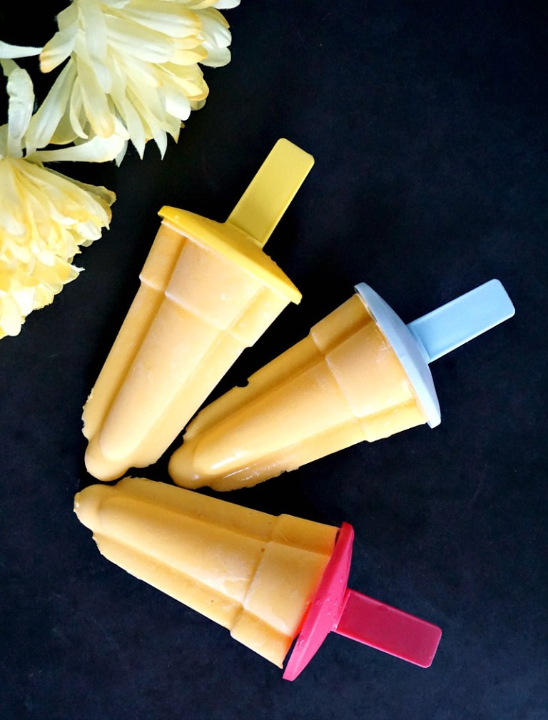 Overhead shot of 3 mango lassi popsicles with 2 flowers next to them