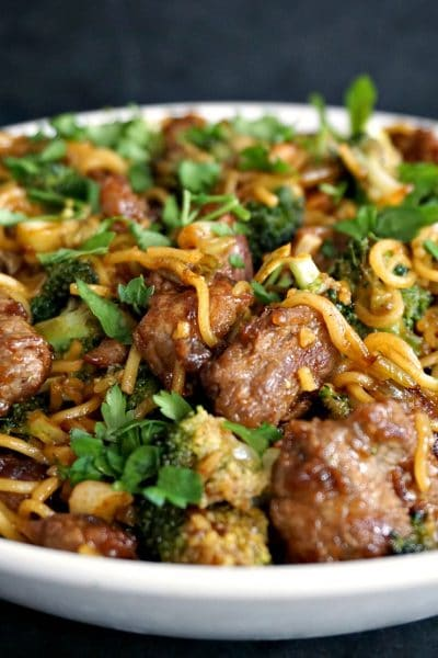 Close-up shoot of a white plate with broccoli and beef noodles