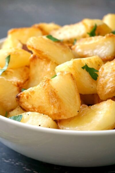 Close-up shoot of a white bowl with roast potatoes