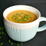 A mug with red lentil sweet potato soup garnished with chopped parsley