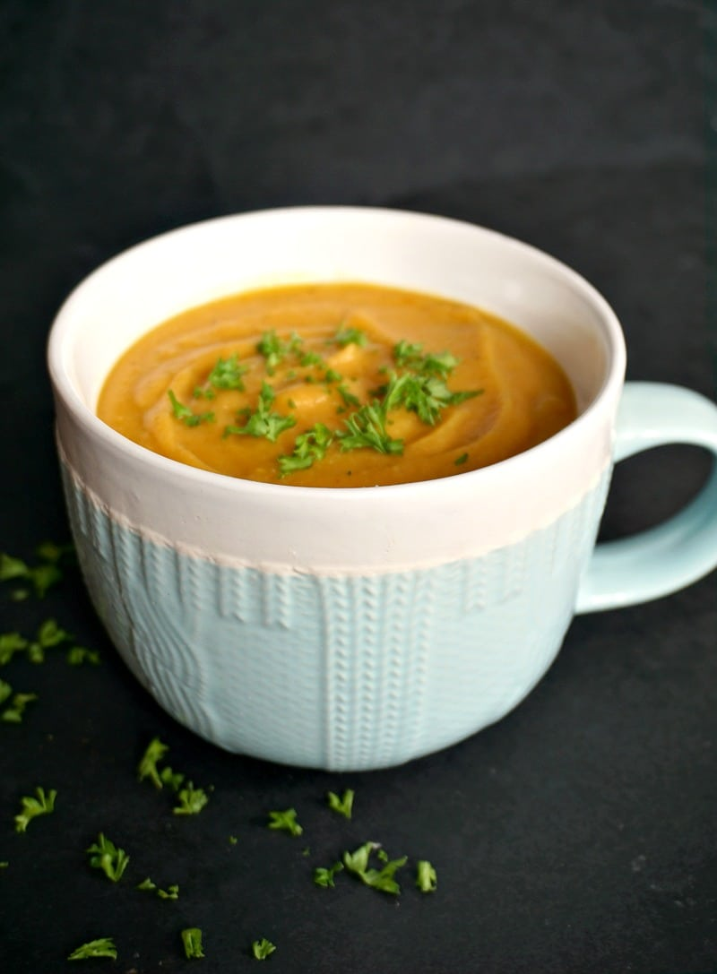 A bowl of sweet potato red lentil soup garnished with parsley