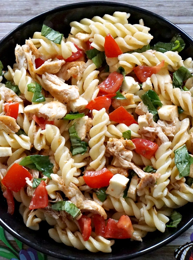 Close-up shot of a black plate of chicken caprese pasta