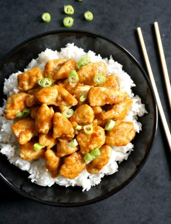 Overhead shoot of a black plate with orange chicken and rice