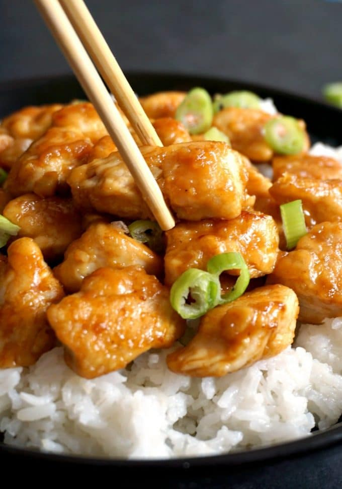 A black plate of rice and orange chicken pieces with chopsticks grabbing one piece