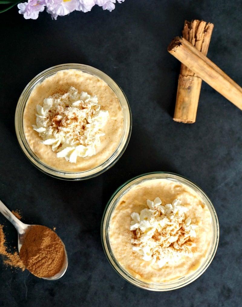 Overhead shoot of 2 pots of sweet potato cheesecakes with 2 cinnamon sticks and a teaspoon of ground cinnamon