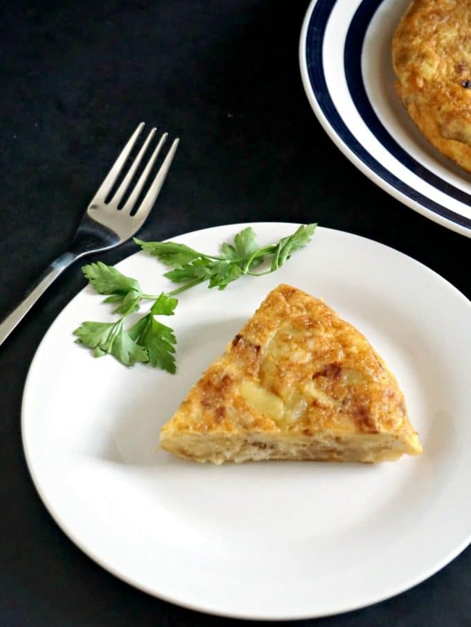 A white plate with a slice of tortilla espanola