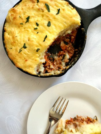 Overhead shot of a skillet with turley shepherd's pie and a white plate with pie and a fork next to it