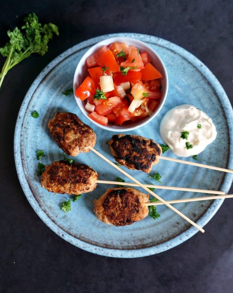 Overehead shoot of a blue plate with 4 turkey kofta skewers and a bowl of tomato salad